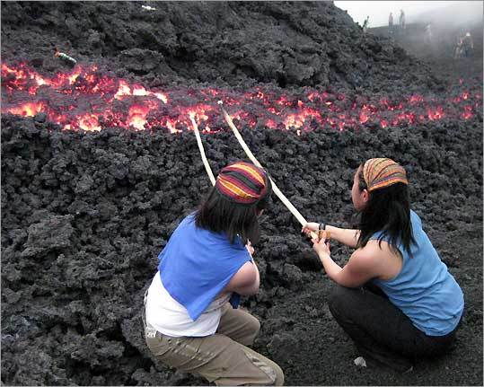 The author (left) and Amy Cheng roast marshmallows over a lava flow from Pacaya volcano among their birthday adventures in Guatemala.
