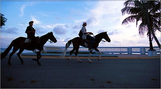 Vieques residents ride their horses down the Malecon in the village of Esperanza in Vieques, Puerto Rico. Navy bombings, Puerto Rican politics, and environmental lawsuits have brought Vieques an agitated sort of fame. But look beyond all that, and you may find a laid-back little island trying to carve out a calmer niche as a tranquil tourist destination.