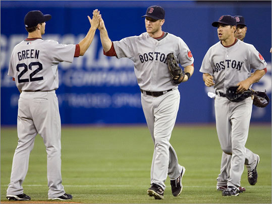 Red Sox players (left to right) Nick Green, Jason Bay, Jacoby Ellsbury, and Alex Gonzalez celebrate the team's 6-1 victory over the Toronto Blue Jays at the Rogers Centre on Wednesday,