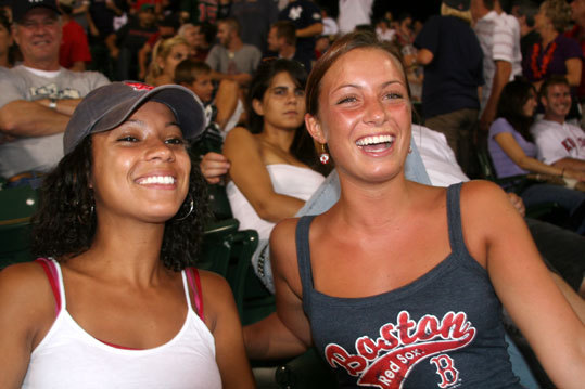 Correy Coleman (left) and Rachel Stavros, both from Quincy, were still managing to enjoy themselves in the bleachers while the Yankees ran up the score on the hometown team.