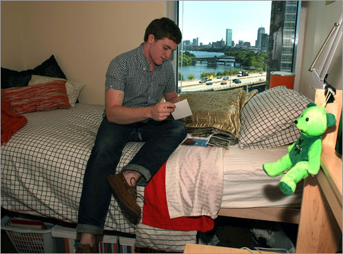 Joseph Nangle, a sophomore from Nyack, N.Y., looks at family photos from his suite-style dorm.