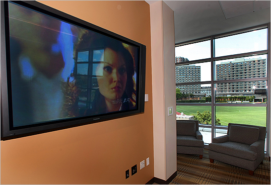 A large plasma TV hangs on the wall in a rec room overlooking the athletic field of West Campus.