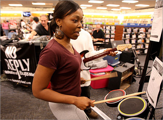 Samantha Fontellio of Cambridge attended a midnight promo for the release of The Beatles: Rock Band game at a Malden Blockbuster Tuesday night. The game, designed by Cambridge's Harmonix Music System features guitars, drums, and microphones as controllers.