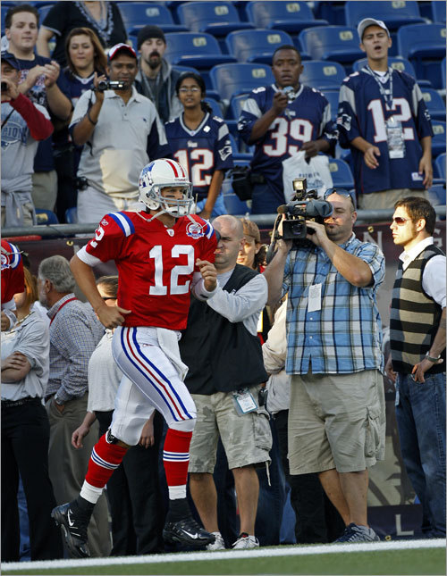 Patriots quarterback Tom Brady is the center of attention as he makes his way onto the field for pregame warm-ups.