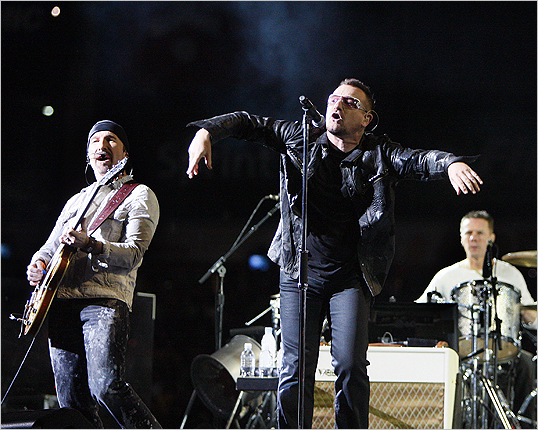 Bono tilted forward and spread his arms as he sang into the microphone.