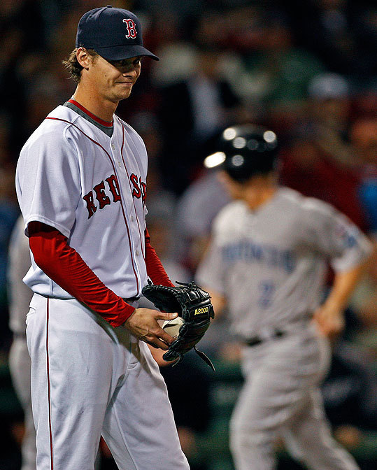 Red Sox starter Clay Buchholz looked dazed after Adam Lind of the Blue Jays became the second of the first three batters of the game to hit a home run off of him, driving in Aaron Hill (in background). The Sox would rally in the game, thanks in part to a three-run homer by J.D. Drew in the eighth, but they still fell short, 8-7. Luckily for the Red Sox, the Rangers also lost their game to the Angels early this morning, helping the Red Sox clinch the AL wild card.