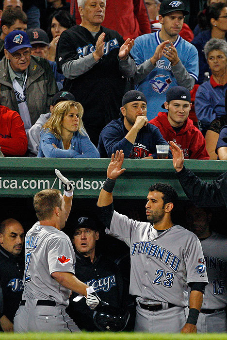 Sox fans in the front row looked glum while Blue Jays fans cheered, and Hill (left) was congratulated by teammate Jose Bautista after his home run.