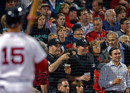 Two fans dressed as umpires enjoyed their beers behind home plate between innings as they waited for Dustin Pedroia to step to the plate.