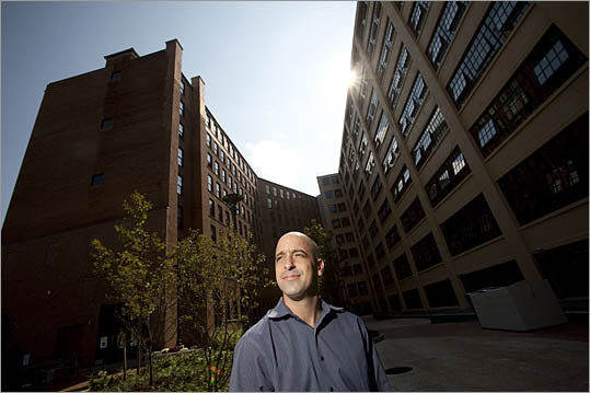 On the once contaminated site of a decaying shoe factory, a thriving neighborhood is growing with the opening of a 305-unit, four-building apartment complex in downtown Haverhill. Douglas J. Arsham, director of development for the Forest City Residential Group, stands in front of Hamel Mill Lofts, part of hundreds of new residential units being built in the city spurred by state and federal incentives.