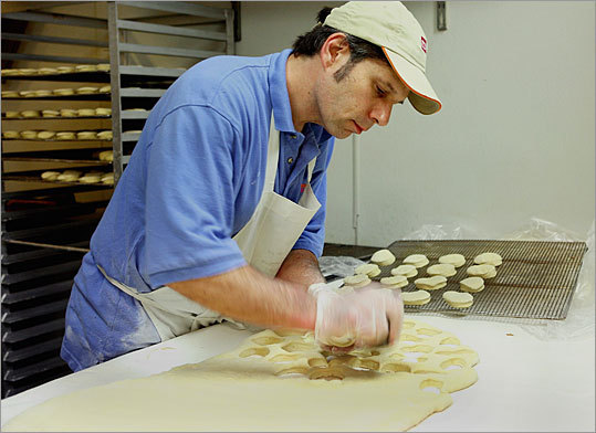 As classical music plays in the background, baker Russ Glod spends his mornings rolling, frying, and frosting hundreds of the circular concoctions for the busiest Dunkin' Donuts store in the nation. Here, Glod hand-cuts the dough for filled doughnuts.