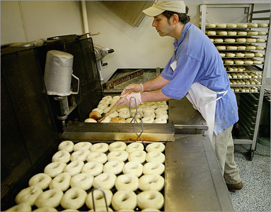 Making the doughnuts on-site has allowed the Weymouth Dunkin' Donuts to feature an expansive selection of more than 35 doughnuts, compared to 20 varieties typically available at Dunkin' shops. Shown here, Glod deep-fries a batch of doughnuts.