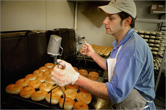 Glod, who has worked at the Weymouth Dunkin' Donuts for more than 25 years, removes a batch of doughnuts from the frialator - a huge vat that contains 150 pounds of oil.