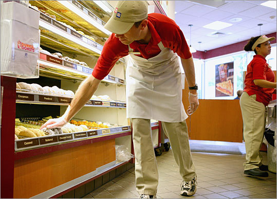 Dunkin' Donuts employee Jim Burke replenishes empty trays of donuts inside the store. The doughnut output nearly doubles on weekends when families trek out to the Weymouth store from across the South Shore.