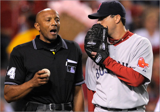 Home plate umpire CB Bucknor and Boston Red Sox starting pitcher Josh Beckett have a discussion between innings.