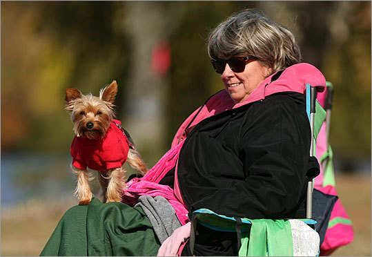 Caryn Daloie from Bronx, NY, sits with her dog, Addie, on the banks of the Charles River near the Riverside Boat Club waiting for her daughter to pass by in the Women's Club Singles race.