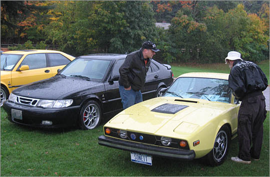 Two visitors check out a 1974 Saab Sonett, the last model year of these limited-production coupes.