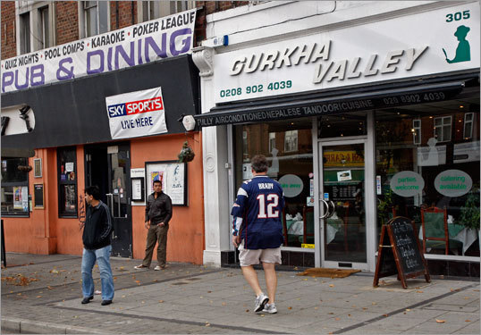 Another Patriots-clad Brady fan walked past some English pubs on the way to this American football game.