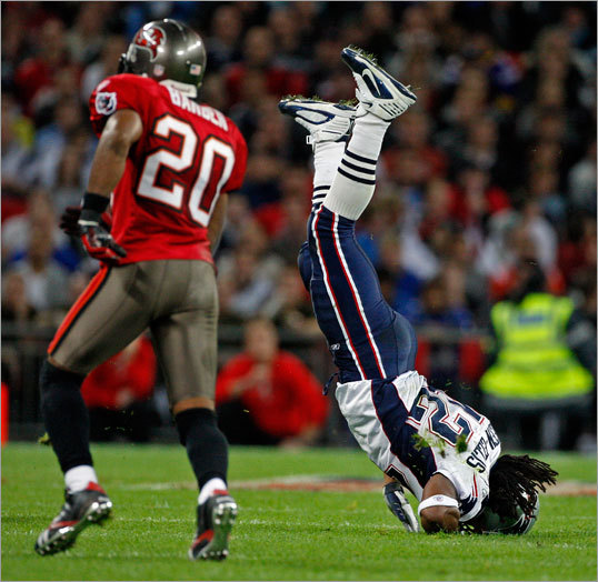 Patriots running back BenJarvus Green-Ellis flipped upside down after a run, the Bucs' Ronde barber is at left.
