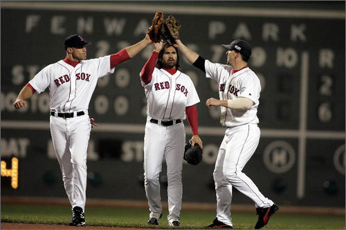 With the final score of Game 2 posted on the Green Monster behind them, outfielders (left to right) Gabe Kapler, Johnny Damon, and Trot Nixon celebrate their 2-0 World Series lead after beating the Cardinals 6-2. Jason Varitek gave the Sox a 2-0 first-inning lead with a two-run triple, and Curt Schilling, blood seeping through his sock after the sutures on his injured ankle again broke, earned the victory.