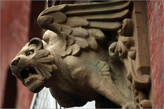 A gargoyle protruding over a copper drain pipe on the exterior of the Church of the Advent.