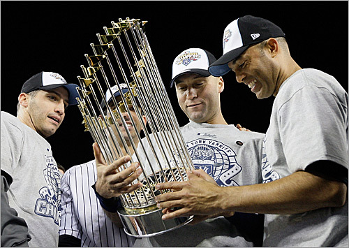 From left: Andy Pettitte, Jorge Posada, Derek Jeter and Mariano Rivera of the New York Yankees celebrated with the trophy after defeating the Phillies, 7-3, in Game 6 to capture the World Series championship.