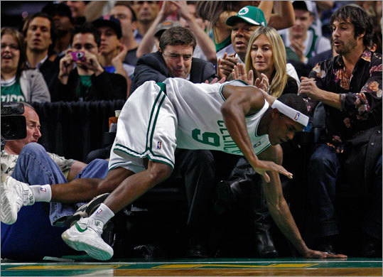 Celtics owner Wyc Grousbeck and his wife Corinne braced for a posible collision as Rajon Rondo fells in front of them after scoring on a drive to the basket in the first half. No one was injured on the play.