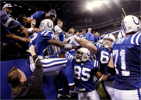 Colts receiver Reggie Wayne celebrated his game-winning touchdown with teammates and fans in the fourth quarter of the Colts' game against the Patriots at Lucas Oil Stadium Sunday in Indianapolis. The Colts defeated the Patriots 35-34.