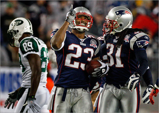 Patriots cornerback Leigh Bodden (left) smiled and pointed skyward after his second interception of the game. Teammate Brandon Meriweather is at right, Jets receiver Jerricho Cotchery is at far left.