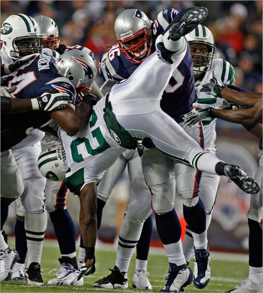 Patriot linebacker Adalius Thomas (96) picked up and flipped Jets running back Shonn Greene as he stopped him on a first-quarter rushing attempt.