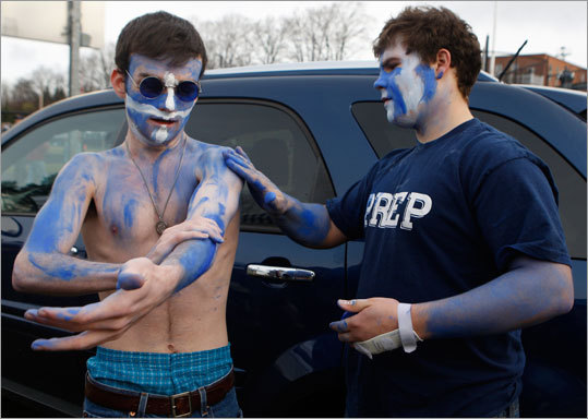 St. John's Prep students Tony Brown, left, and Stash Usouicz put on body paint before their team plays Xaverian.