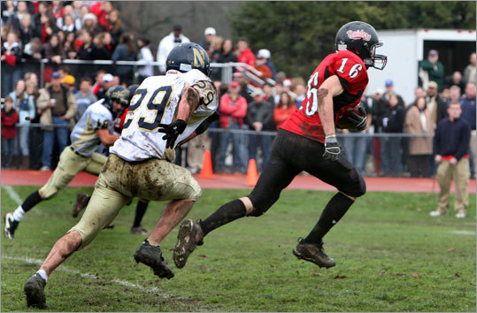 Wellesley High School's Sam Lawrence (16) took off for the end zone as Needham's Greg Angel (29) pursued.