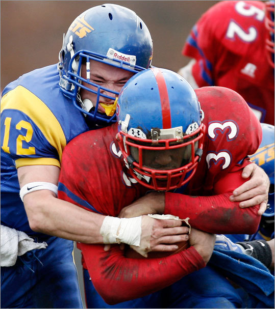 In a reversal of roles, East Boston's Brandon Amodeo (12) wraps up South Boston running back Daquan Hill.