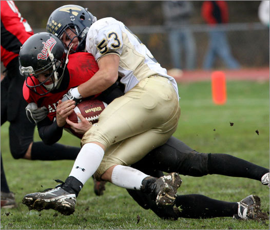 Wellesley High School's quarterback Brendan Brooks (17) was brought down by Needham's Charlie Kenslea (53) during the two team's Thanksgiving Day game in Wellesley.