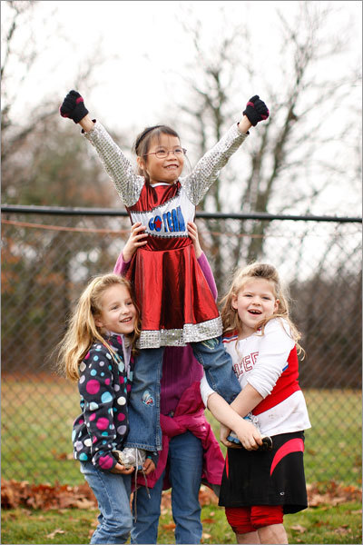 A group of Holliston girls practiced their cheers from the sidelines during the game. From left: Sophia Loricco, 6, Mae Rayner, 7, and Grace Kilkelly, 6. Holding Mae from the back is Lara Daniels, 5.