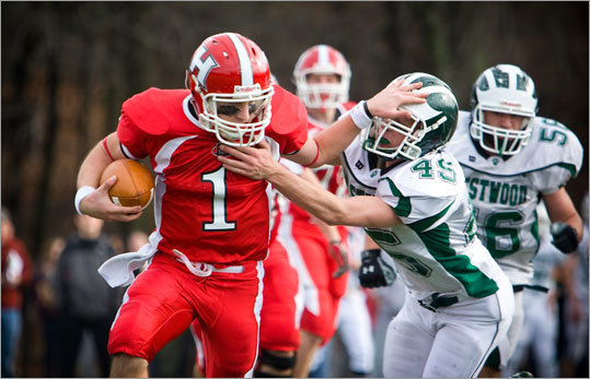 Holliston junior Sean Mayo, left, tried to outrun a tackle by Westwood senior Tommy Ahearn.