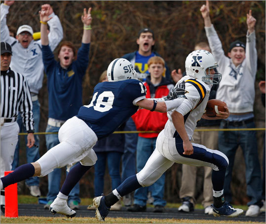Xaverian's quarterback Alex Phelan beat St. John's Prep Kevin Davis to the end zone on a rushing touchdown during the first quarter.