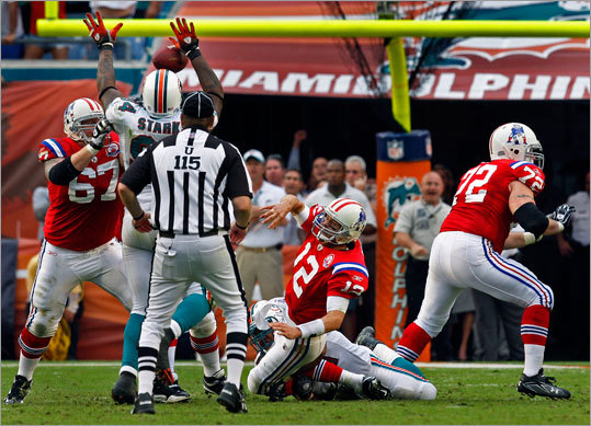 Patriots quarterback Tom Brady was dragged down by Dolphins linebacker Cameron Wake as he threw his final pass attempt. It was intercepted, and the Dophins defeated the Patriots 22-21.