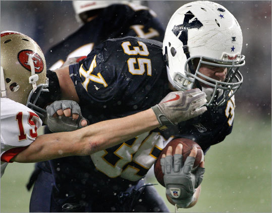 Xaverian's Matt Tuleja (right) broke the tackle of Everett's Matt Costello.