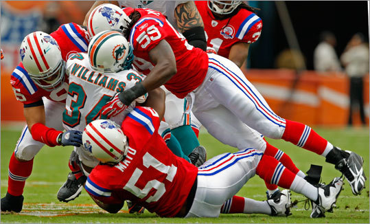 Dolphins running back Ricky Williams was brought down by Tully Banta-Cain, Jerod Mayo and Gary Guyton in the first quarter.