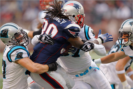 New England Patriots running back Laurence Maroney (39) was surrounded by Carolina Panther's defenders Jordan Senn, left, and Hilee Taylor.