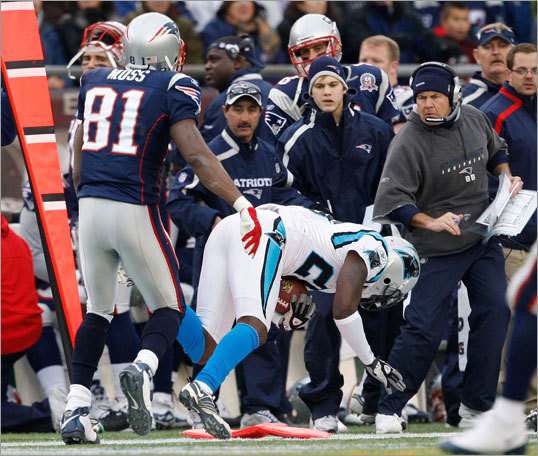 Carolina's Chris Gamble (right) almost plowed into Patriots head coach Bill Belichick after he picked off a Tom Brady pass intended for Randy Moss (left).