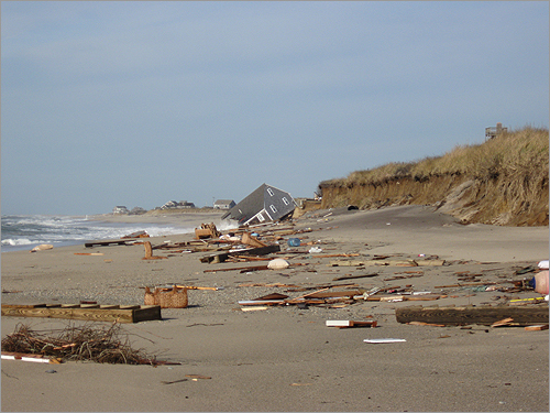 Work crews on a Nantucket beach Wednesday removed remnants of a house that slipped into the Atlantic Ocean this week. Take a look at photos of the house and the debris.