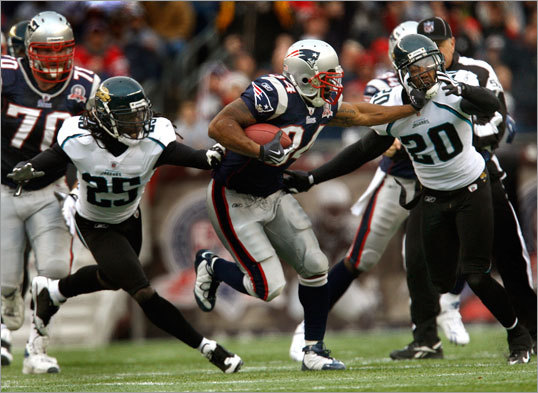 Patriots running back Sammy Morris (34) straight-armed Jacksonville safety Anthony Smith (20) en route to breaking loose for a long gain in the second quarter.