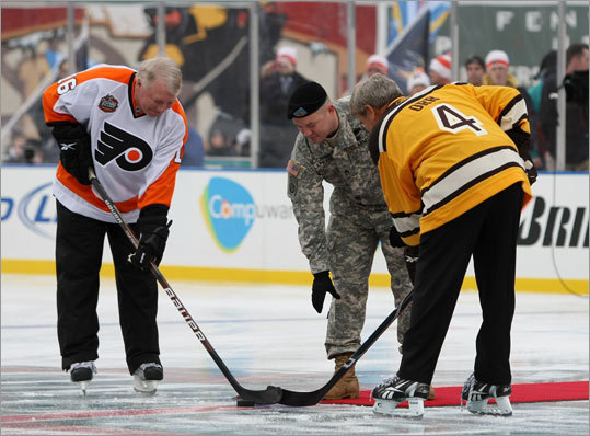 Staff Sergeant Ryan R. LaFrance (center) dropped the ceremonial first puck for with Flyers great Bobby Clarke and Bruins great Bobby Orr before the Winter Classic began Friday at Fenway Park.