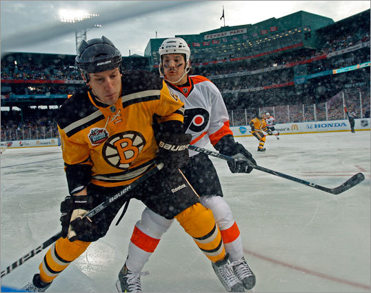 Boston's Byron Bitz (left) and the Flyers' Dan Carcillo (right) battled along the boards in the third period.