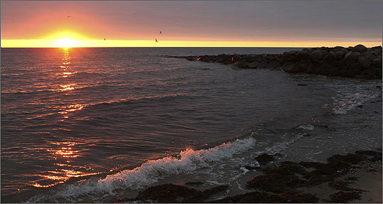 In this Friday, Oct. 30, 2009, file photo, the sun begins to rise over Nantucket Sound as seen from Popponesset Beach in Mashpee.
