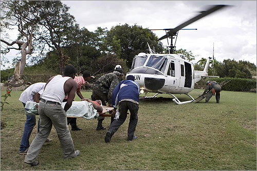 Haitians and United Nations peacekeepers loaded an injured woman into a helicopter.