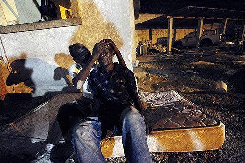 Gunsly Milsoit, left, comforted his brother-in-law Leo Pierre after Leo's wife and Gunsly's sister, Milsoit Kelly, who was three months pregnant, died in a four-story building collapse.