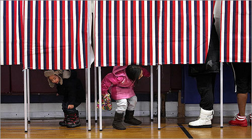 Maximus Vo, 2, left, and his 5-year-old sister, Trinity Vo, played in the booths while their mother, Trang Vo, voted in Dedham.