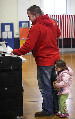 Sophie Minihane, 2, stayed close to her father, Patrick Minihane, as he fed his ballots into the machine after voting in Dedham.